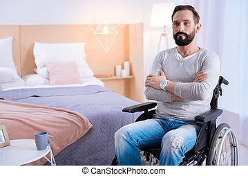 Serious paralyzed man having his arms crossed