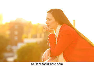 Serious pensive woman in a balcony in winter at sunset