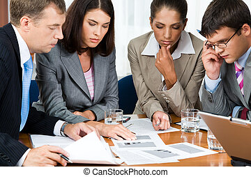 Serious people - Photo of business group sitting at the...