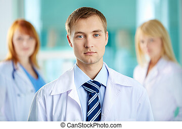 Serious physician - Portrait of serious clinician in white...
