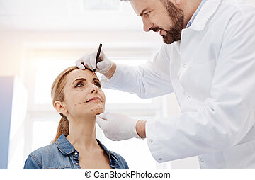 Serious plastic surgeon drawing marks on his patients face
