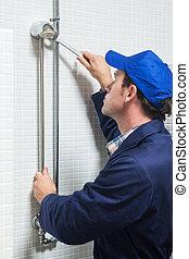 Serious plumber repairing shower head