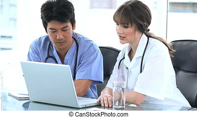 Serious practitioners talking together in front of a laptop