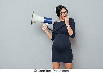Serious pregnant business lady holding loudspeaker. - Photo ...