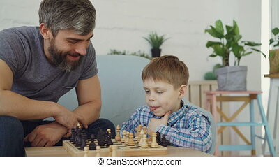 Serious preschool child is playing chess with his parent...