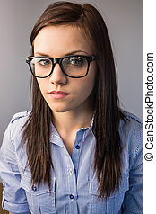 Serious pretty brunette wearing glasses posing on grey...