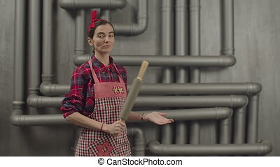 Serious pretty housewife holding rolling pin - Serious...