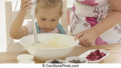 Serious pretty little girl concentrating on baking