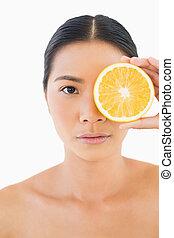 Serious pretty woman holding orange slice