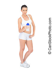 Serious pretty woman in sportswear holding flask