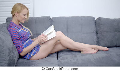 Serious Pretty Woman Reading a Book on the Sofa