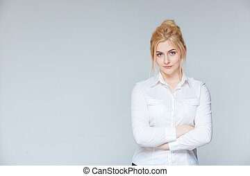 Serious pretty young businesswoman standing with arms crossed