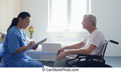 Serious professional female doctor talking with a wheelchaired aged man