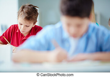 Serious pupil - Portrait of serious schoolboy drawing at...