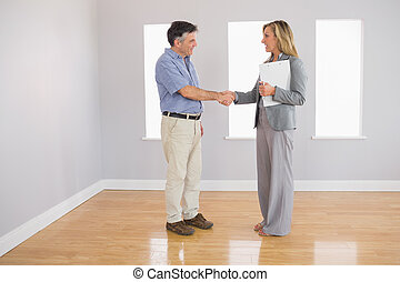 Serious realtor shaking the hand of her buyer - Serious...