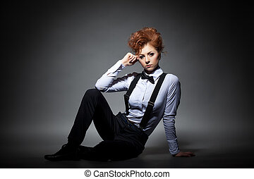 Serious red-haired woman posing in office suit