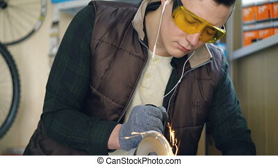 Serious repairman in safety goggles is using electric...
