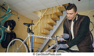 Serious repairman is fixing bicycle with screw wrench and...