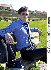 Serious sad business man sitting on bench looking