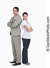 Serious salesteam with arms folded standing back to back