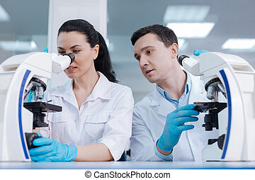 Serious scientist looking at the process of his colleague