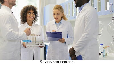 Serious Scientist Woman Discuss Chemicals With Her team Making Notes Researchers Group Working In Laboratory