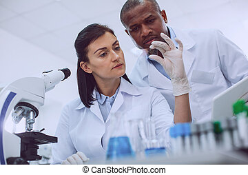 Serious scientists looking at a sample