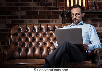 Serious self employed man working on the laptop