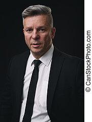 Serious senior businessman in black suit