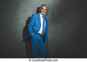 Serious Senior Businessman Leaning Against Wall