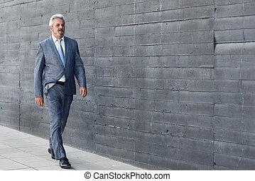 Serious senior businessman walking outside of modern office building.