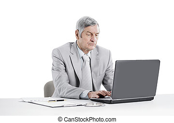senior businessman working on laptop while sitting at his Desk