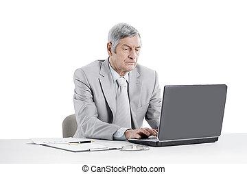 senior businessman working on laptop while sitting at his Desk