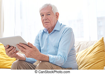 Serious senior man in casualwear looking at you while using digital tablet