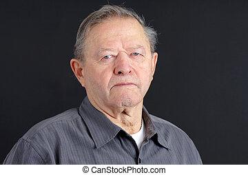 Serious senior man on black