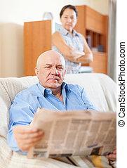 serious senior man reading newspaper