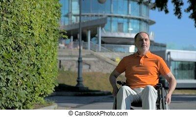 Serious senior man using wheelchair outdoors