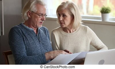 Serious senior mature couple disputing holding paper bills checking finances