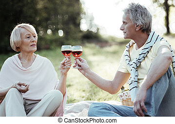 Serious senior woman going to drink wine