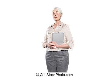 Serious senior woman holding digital tablet and looking at camera