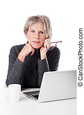 Serious senior woman with her laptop