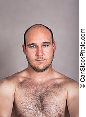 Serious shirtless man with his hairy chest