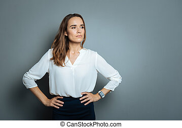 Serious smart businesswoman resting hands on her hips -...