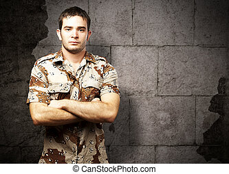 portrait of a serious young soldier standing against a vintage bricks wall