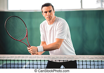 Serious sportsman playing tennis on court