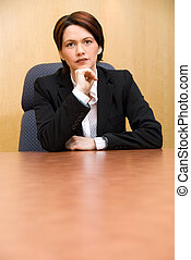 Serious - serious business woman in a boardroom table