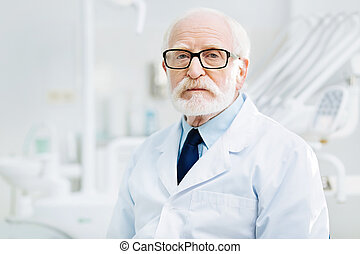 Serious stomatologist standing in dental cabinet - Being...