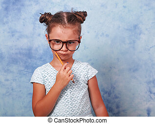 Serious strict kid girl in eye glasses holding pencil and thinking about with trendy hair style on blue background