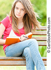 serious student girl sitting on bench with book