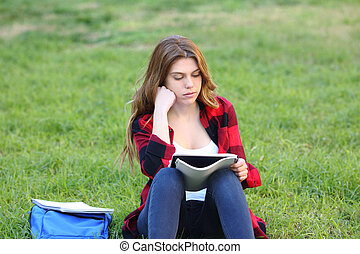 Serious student studying reading notes on the grass